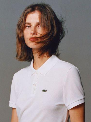 Logo brand Lacoste di sisi kiri polo shirt.