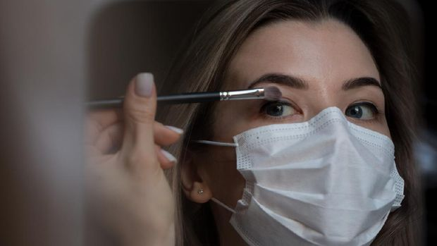 girl in medical mask against coronovirus does eye makeup. Covid-19. Covid-20. Young women make-up in beauty salon.