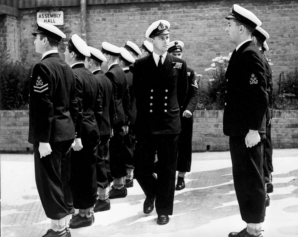 FILE - In this July 31, 1947 file photo, Lieut. Philip Mountbatten, as he was then called, center, inspects his men at the Petty Officers' Training Center at Corsham, England. There certainly won't be fuss. Count on that. When Britain's Prince Philip reaches the grand age of 99 on Wednesday, he will spend it quietly and in much the same way he's spent most of his adult life: beside Queen Elizabeth II. (AP Photo/File)