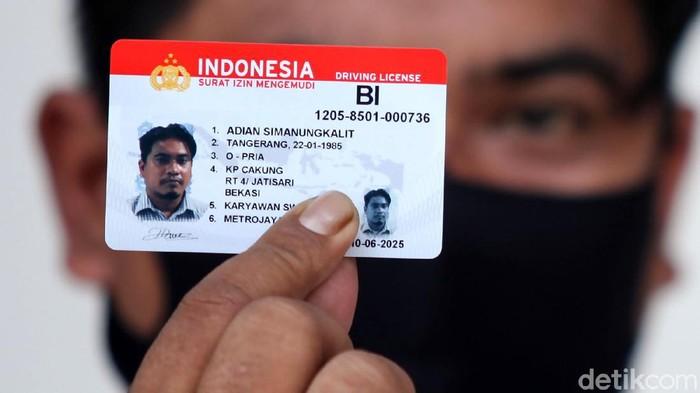 Seorang petugas tengah melayani warga yang ingin mengurus Surat Ijin Mengemudi (SIM) di Satpas Daan Mogot, Jakarta Barat, Rabu (10/6/2020). Saat pandemi Corona ini, pelayanan pembuatan SIM di Satpas menerapkan protokol kesehatan.
