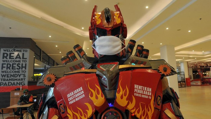 Replika robot transformer menggunakan masker dan memasang imbauan jaga jarak di Transmart Padang, Sumatera Barat, Selasa (9/6/2020). Mall terbesar di Padang itu menerapkan protokol kesehatan mencegah penyebaran COVID-19 yakni dengan menyediakan tempat cuci tangan, pemeriksaan suhu tubuh, penggunaan pelindung wajah dan sarung tangan bagi pekerja, serta melarang pengunjung yang tidak memakai masker untuk masuk. ANTARA FOTO/Iggoy el Fitra/hp.
