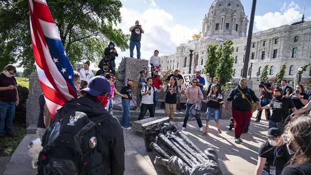 People kick at the head of a Christopher Columbus statue that was torn down at the Minnesota state Capitol in St. Paul, Minn., Wednesday, June 10, 2020. (Evan Frost/Minnesota Public Radio via AP)