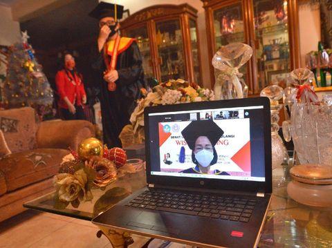 Pandemi COVID-19 membuat acara wisuda Universitas Sam Ratulangi digelar secara daring. Pemindahan tali toga pun dilakukan oleh orang tua wisudawan.