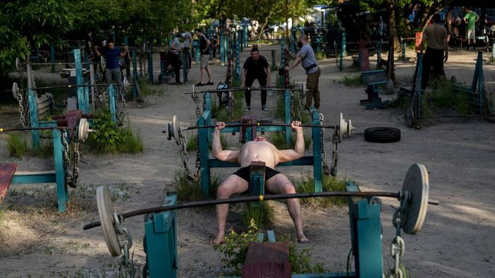 In this photo taken on Sunday, June 7, 2020, a man trains in the outdoors gym on the Dolobetskiy island on the Dnipro River in Kyiv, Ukraine. Relishing an opportunity to do exercise after a long lockdown, hundreds of Kyiv residents flock to an improvised outdoor workout on an island facing the Ukrainian capital. The Kachalka gym on the Dolobetskiy island on the Dnipro river has enjoyed broad popularity ever since it opened in 1966. (AP Photo/Evgeniy Maloletka)