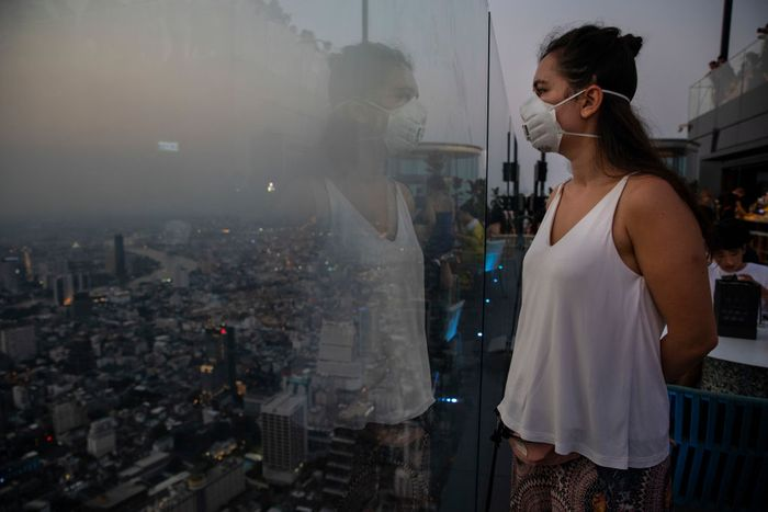 BANGKOK - JANUARY 14 : Roxana Ionicioiu from Romania wears mask at the 78-floor mirrored skyscraper viewing deck King Power Mahanakhon tower in Bangkok, Thailand on January 14, 2020. Thick, unhealthy smog continues to plague much Bangkok and the North, with the worst pollution in Lampang province near Chiang Mai. According to the Pollution Control Dept  unsafe levels of particulate matter 2.5 micrometres and less in diameter (PM2.5) at 11 of the 15 air quality measurement stations it operates in the North. (Photo by Paula Bronstein/Getty Images )
