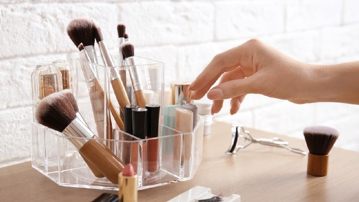 Woman taking lipstick from organizer for makeup cosmetic products on dressing table