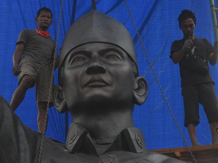 Pekerja memasang patung Presiden pertama sekaligus Proklamator Kemerdekaan Republik Indonesia (RI) Soekarno di Taman Gor di Palu, Sulawesi Tengah, Kamis (11/6/2020). Patung berbahan tembaga setinggi delapan meter tersebut didirikan di lokasi kedatangan dan pidato Soekarno di Kota Palu pada tahun 1957. Keberadaan tempat dan patung yang diberi nama sebagai Monumen Mutiara Bangsa tersebut diharapkan memperkuat rasa nasionalisme serta menjadi salah satu ikon wisata daerah tersebut. ANTARA FOTO/Mohamad Hamzah/aww.