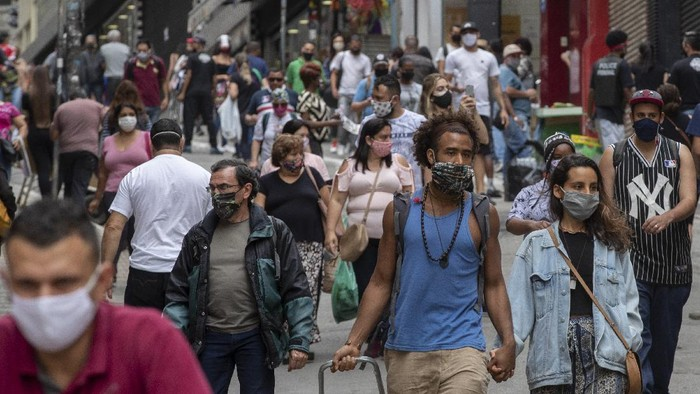 People walk through a downtown shopping district in Sao Paulo, Brazil, Wednesday, June 10, 2020. Retail shops reopened on Wednesday in Brazils biggest city after a two-month coronavirus pandemic shutdown that aimed to contain the spread of the new coronavirus. (AP Photo/Andre Penner)