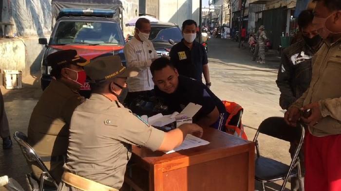 Petugas Gabungan pengawasan PSBB menggelar razia di Pasar kebayoran lama. Mereka yang tak menggunakan masker langsung dirusuh menyapu jalanan.