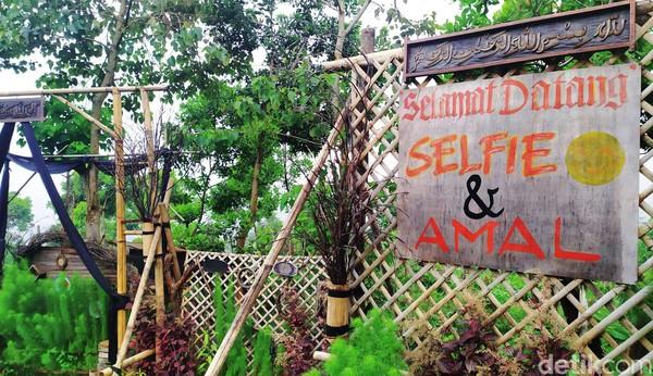 Tertera papan bertuliskan Selamat Datang, Selfie dan Amal di depan pintu masuk menuju spot berfoto tersebut.
