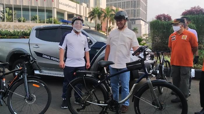 Gubernur DKI Jakarta Anies Baswedan, Wagub A Riza Patria bersepeda di kawasan Bundaran HI, Minggu (14/6/2020).