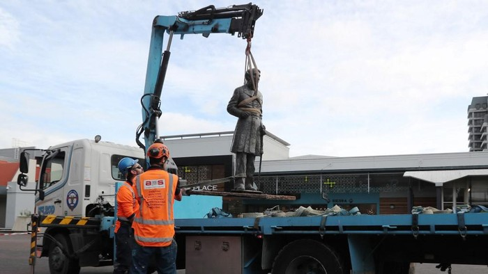 Workers remove a controversial statue of Captain John Fane Charles Hamilton from Civic Square in Hamilton on June 12, 2020, following a formal request by the Waikato-Tainui iwi (tribal confederation) and threats it would be torn down during a Black Lives Matter march due to take place the following day. - The statue of Hamilton, a British military commander who led a detachment against Maori during the Battle of Gate Pa in 1864, was removed as statues of colonial figures in Britain, Belgium and the United States were toppled by demonstrators amid worldwide protests against police brutality and racism in the wake of African American George Floyds killing by a white police officer. (Photo by MICHAEL BRADLEY / AFP)