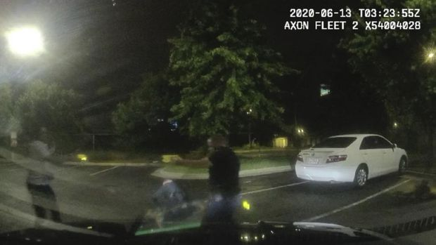 This screen grab taken from dashboard camera video provided by the Atlanta Police Department shows Rayshard Brooks, left, and Officer Garrett Rolfe pointing Tasers at one another, while Officer Devin Brosnan is seen getting up after a struggle among the three men in the parking lot of a Wendy's restaurant, early Saturday, June 13, 2020, in Atlanta. Rolfe has been fired following the fatal shooting of Brooks and Brosnan has been placed on administrative duty. (Atlanta Police Department via AP)
