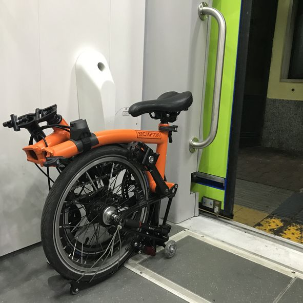 Turin, Italy - October 10, 2018: The Brompton Black Special Edition completely folded in Turin. Brompton bikes are quite popular between commuters due to the fact that they can be easily folded and stored on public transports.The picture was taken in the city of Turin in the surroundings of the station. The bike is folded because the owner is about to carry it on a train. This is the smaller possible fording configuration for the Brompton.