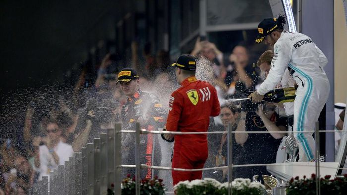 ABU DHABI, UNITED ARAB EMIRATES - DECEMBER 01: Top three finishers Lewis Hamilton of Great Britain and Mercedes GP, Max Verstappen of Netherlands and Red Bull Racing and Charles Leclerc of Monaco and Ferrari celebrate on the podium during the F1 Grand Prix of Abu Dhabi at Yas Marina Circuit on December 01, 2019 in Abu Dhabi, United Arab Emirates. (Photo by Charles Coates/Getty Images)