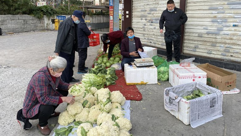 Fuzhou, Fujian, China. On February 29, 2020, vendors sold vegetables at the closed shop door. Due to the outbreak, the government closed the market.