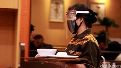 Penerapan protokol kesehatan turut diterapkan di sejumlah rumah makan. Para pramusaji pun diwajibkan pakai masker saat bekerja.