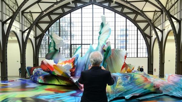 Seorang pengunjung mengabadikan karya seni tersebut menggunakan gatget mereka.