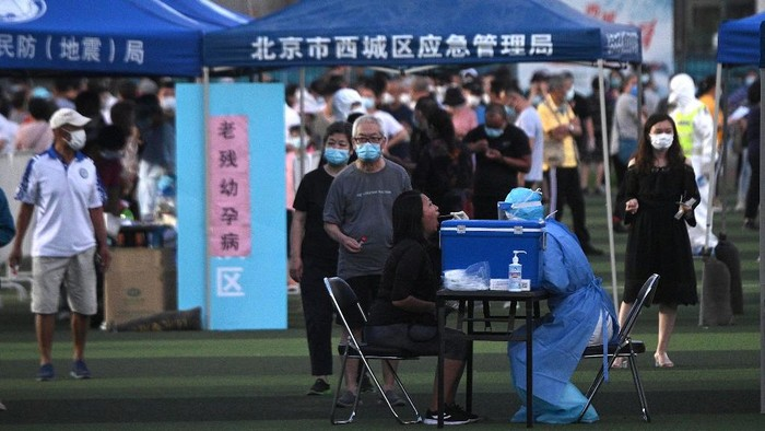 A health worker wearing a protective suit takes a swab test from a woman at Guangan Sport Center for people who visited or live near the Xinfadi Market in Beijing on June 14, 2020. - The domestic COVID-19 coronavirus outbreak in China had been brought largely under control through strict lockdowns that were imposed early this year -- but a new cluster has been linked to Xinfadi market in south Beijing. (Photo by Noel Celis / AFP)