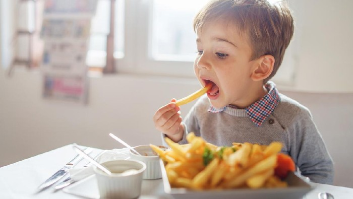 Portrait of small little cute caucasian boy kid eating french fries potato chips at the table in the restaurant or at home three or four years old