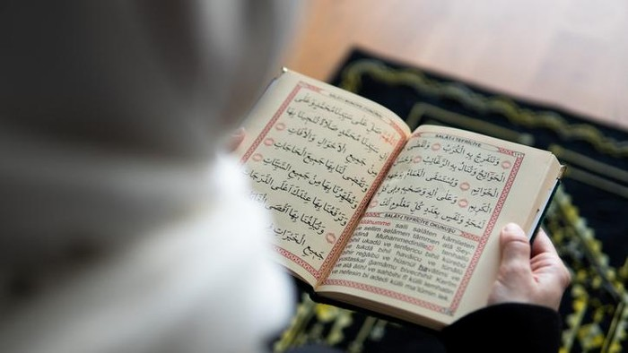 Muslim woman reading from the quran stock photo