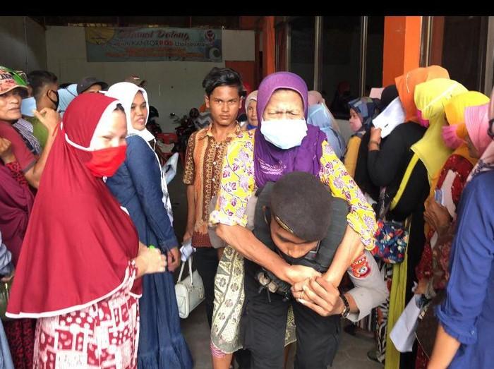 Bripda Agus Ganto membopong seorang nenek lumpuh untuk mengambil BLT.