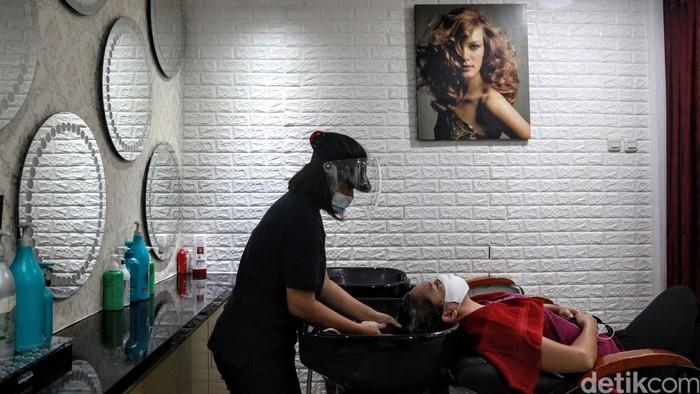 Hairstylist dengan memakai APD beraktivitas di salon kecantikan Guzell di Bintaro, Tangsel, Banten. Pelonggaran PSBB dimanfaatkan pelaku UKM untuk memulihkan ekonomi.