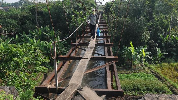 Seorang warga melewati papan kayu yang dipasang pada jembatan irigasi di Ngemplak, Boyolali, Jawa Tengah, Selasa (16/6/2020). Menurut warga setempat, jembatan yang telah dibangun pada zaman Belanda tersebut digunakan sebagai saluran irigasi untuk kebutuhan pengairan pertanian di wilayah tersebut. ANTARA FOTO/Aloysius Jarot Nugroho/foc.