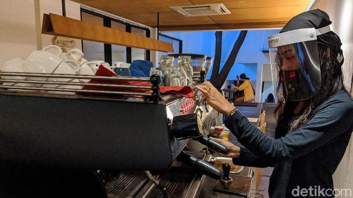 Barista menyajikan menu kopi di coffee shop Kopi Manyar, Bintaro, Jakarta Selatan, Selasa  (16/6/2020).  Coffee shop yang didesain oleh arsitek beken Andra Matin tersebut kembali melayani layanan makan di tempat (dine in) dengan menerapkan tatanan normal baru dengan menjalankan protokol kesehatan guna mencegah penularan COVID-19. Layanan dine in mulai dilakukan sejak Senin (15/6) sesuai aturan PSBB transisi pemerintah.
