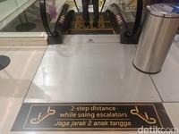 Setiap pengunjung wajib menjaga jarak di eskalator.