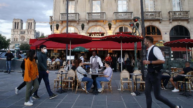People sit on a cafe, Monday, June 15, 2020 in Paris. Paris is rediscovering itself, as its cafes and restaurants reopen for the first time since the fast-spreading virus forced them to close their doors March 14. Restaurants outside the Paris region opened earlier this month, and Paris cafes were allowed to serve people outside but not open their doors. After three months of losses, some restaurateurs fear it will take a long time for business to come back. (AP Photo/Thibault Camus)