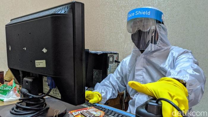 Pegawai Dinas Kependudukan dan Pencatatan Sipil menggunakan pakaian alat pelindung diri (APD) melakukan perekaman data pembuatan KTP Elektronik. Begini potretnya.
