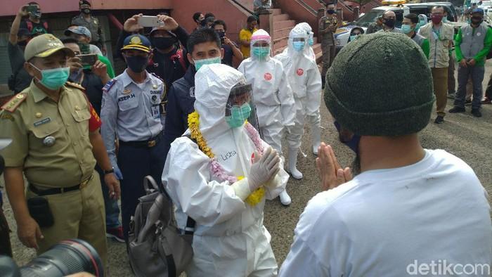 Tim medis disambut kalung bunga oleh pedagang Pasar Cileungsi.