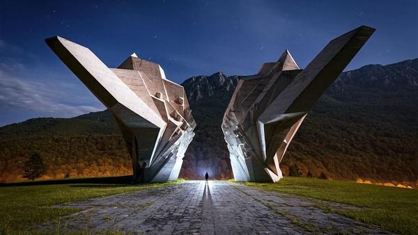 Gambar di sini ditangkap di Monumen Pertempuran Sutjeska di Bosnia dan Herzegovina, dengan cahaya bulan purnama berkilau saat menghantam beton lembab dari monumen WW2. Obor genggam digunakan untuk menerapkan beberapa highlight di sekitar sosok manusianya.