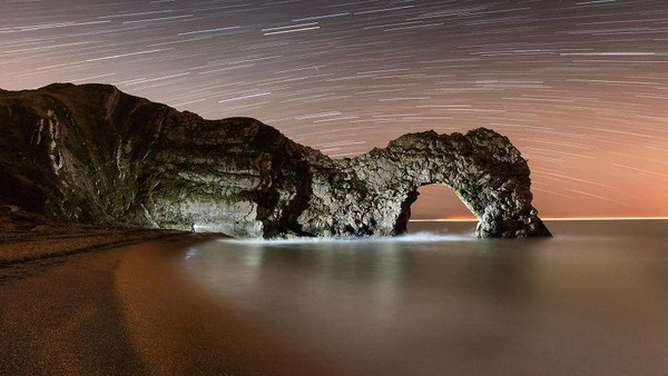 Foto komposit ini menunjukkan pantai yang gelap dan kosong di samping Durdle Door di Pantai Jurassic Dorset, dengan sekitar satu jam rotasi bumi direkam dalam jejak bintang di langit. Jika diperhatikan dengan teliti, Anda mungkin dapat melihat sosok mungil yang sedang menerangi wajah batu dari garis pantai.