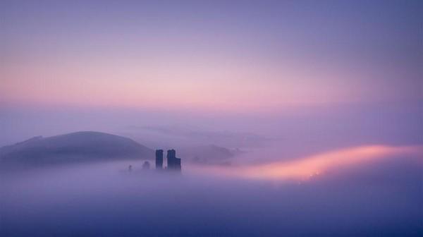 Gambar ini adalah tangkapan beruntung pada perjalanan pulang sang fotografer melewati Kastil Corfe di Dorset. Malam yang basah dan dingin jelas meninggalkan awan-awan kabut yang indah menyelimuti lanskap ketika pagi akan datang.