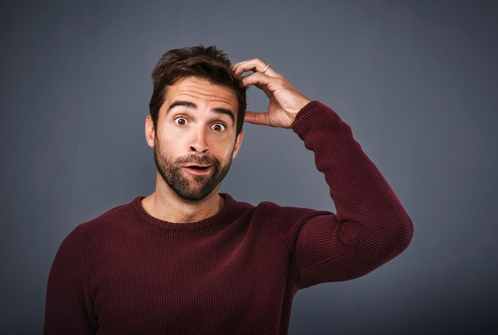 Studio shot of a young man scratching his head in confusion against a gray background