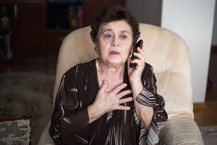 Elderly woman is speaking by her cell phone. She is shocked by the news she has just recieved. Comunication, bad news, critical situation concept.