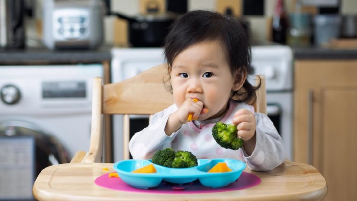 Asian baby girl eating vegetable first time at home kitchen