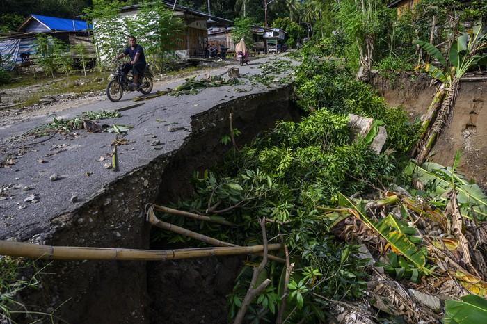 Sejumlah pengendara sepeda motor melintas di jalan yang sebagian ruasnya longsor di Desa Omu, Sigi, Sulawesi Tengah, Kamis (18//6/2020). Dua desa yakni Desa Omu dan Desa Tuva di Kabupaten Sigi diterjang banjir dan longsor akibat intensitas hujan yang tinggi pada Kamis (18/6/2020) dini hari yang erusak pemukiman warga termasuk fasilitas sekolah dan rumah ibadah. ANTARAFOTO/Basri Marzuki/aww.