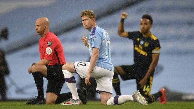 Manchester City's Kevin De Bruyne takes a knee in support of the Black Lives Matter movement before the English Premier League soccer match between Manchester City and Arsenal at the Etihad Stadium in Manchester, England, Wednesday, June 17, 2020. The English Premier League resumes Wednesday after its three-month suspension because of the coronavirus outbreak. (Peter Powell/Pool via AP)