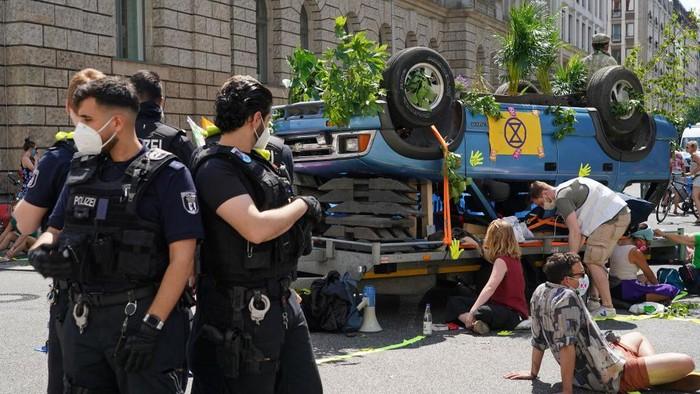 Sejumlah warga gelar demo terkait perubahan iklim di Berlin, Jerman. Sebuah mobil terbalik yang dihiasi dengan sejumlah tumbuhan dan poster ramaikan aksi itu.