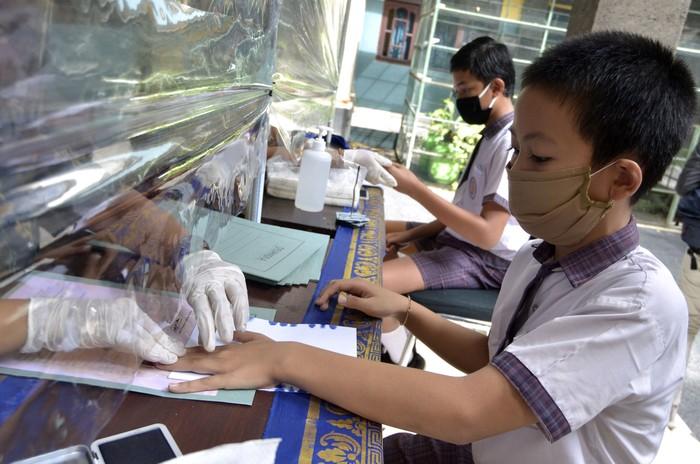 Siswa kelas VI melakukan cap tiga jari saat proses pengambilan dokumen kelulusan di SD Widiatmika, Jimbaran, Badung, Bali, Kamis (18/6/2020). Pengambilan dokumen kelulusan berupa Surat Keterangan Lulus dan Surat Keterangan Hasil Ujian Sekolah yang mengharuskan kehadiran siswa ke sekolah untuk melakukan cap tiga jari tersebut menerapkan berbagai protokol kesehatan seperti pemeriksaan suhu tubuh dan penggunaan hand sanitizer bagi siswa dan orang tua, penggunaan alat pelindung diri bagi guru dan karyawan serta pemasangan pembatas plastik yang membatasi jarak guru dan siswa untuk mencegah penyebaran COVID-19. ANTARA FOTO/Fikri Yusuf/aww.