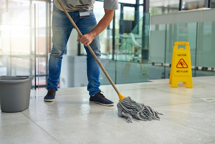 Shot of an unrecognizable man mopping the office floor