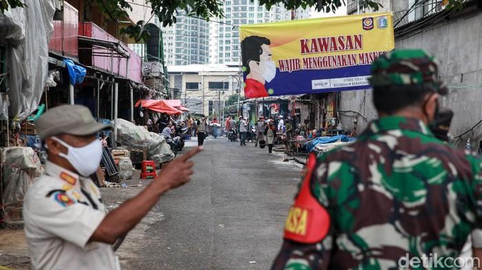 Hari ini merupakan hari kedua penutupan Pasar Kebayoran Lama, Jakarta. Petugas kembali menyemprotkan disinfektan pada area pasar.