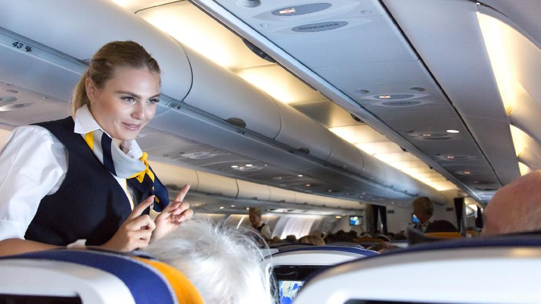 Munich: A female flight attendant  is speaking with a passenger sitting in the economy class of the route Munich - Vancouver of Lufthansa Airlines.
