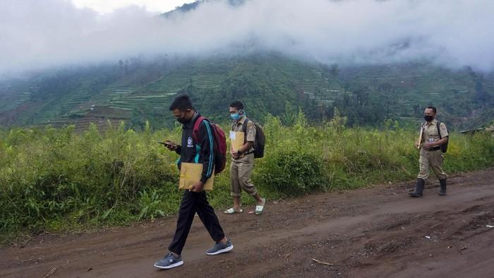 Kepala Sekolah SMP N 4 Bawang Mulud Sugito (tengah) dan guru Wiyata Bhakti bersiap melewati aliran sungai di dasar bukit saat mengantar lembar tugas siswa secara langsung ke rumahnya di Pranten, Kecamatan Bawang, Kabupaten Batang, Jawa Tengah.