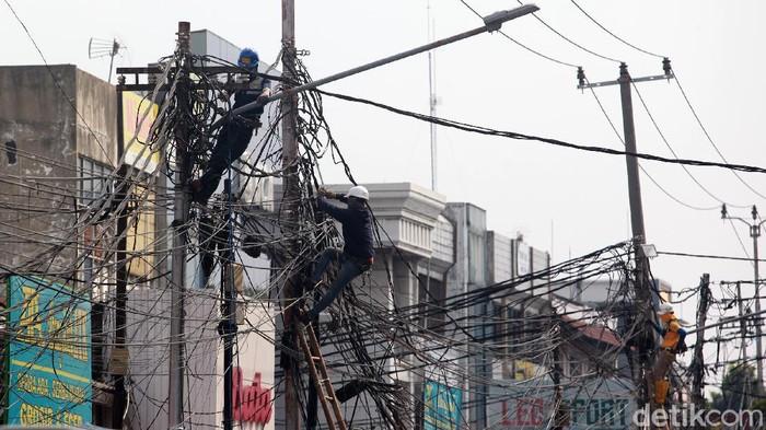 Para pekerja menyelesaikan instalasi jaringan kabel fiber optik di Kebayoran, Jakarta, Kamis (18/6/2020).