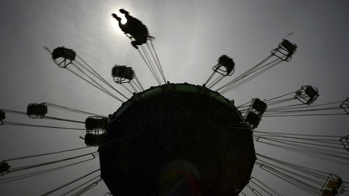 A visitor enjoys the swing ride at the Yomiuriland amusement park in Tokyo, Tuesday, June 16, 2020. The park has been closed since the end of March due to the new coronavirus, has taken measures to prevent infections and reopened limited attractions. (AP Photo/Eugene Hoshiko)