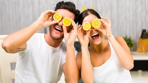 Young man and woman having fun with lemon while having a breakfast.